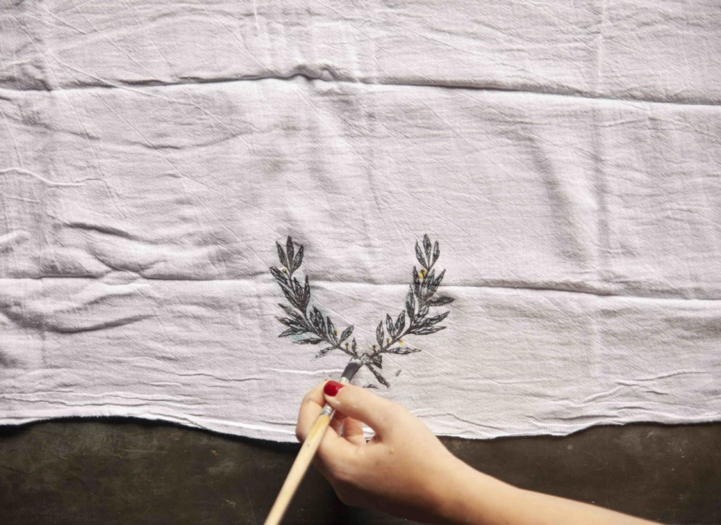 Design and paint your own watercolor tea towel using A Makers' Studio stamps and Gel Art Ink. Make a beautiful laurel, floral tea towel for your kitchen or bathroom!